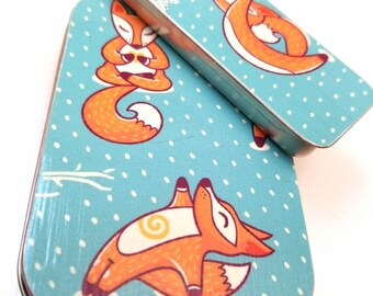 Large hinge tin and medium thin tin duo . . . Yoga foxes in the snow . . .