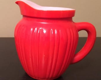 Small, vintage, orange and white milk glass pitcher, creamer, vase