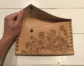 Handmade leather clutch bag, decorated by hand with a floral pyrography pattern.