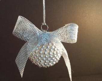 Small glass silver ornaments. This little ornament is wrapped in silver beads and tied with a mesh silver bow.