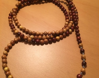A very long handmade wooden beaded necklace to be worn in a triple wind around the neck.