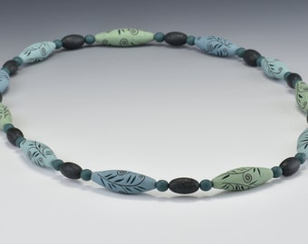 Green, hand-carved necklace of polymer clay