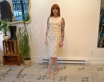 1960's Ivory Floral Lace Shift Dress. Knee Length, Sleeveless, 2 layers. A-line. Scalloped Hem. Ribbon bow in the Front.