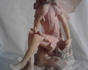 """12"""" Serene Fairy Indoor Statue With Pink Dress Sitting On Stones Holding Flower"""