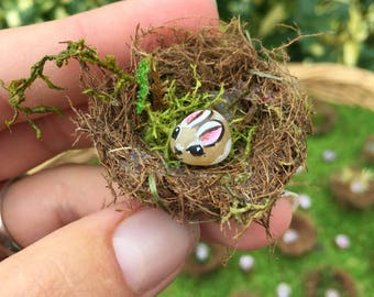 Miniature tiny bunny rabbit hand painted stone in a nest
