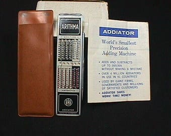 Vintage Arithma World's Smallest Adding Machine, it also Subtracts in it's Original Holder, with it's Original Instructions