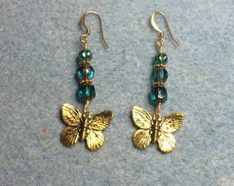 Gold butterfly charm earrings adorned with teal Czech glass beads.