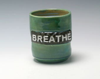 Handmade ceramic yunomi teabowl 10 ounce in emerald green, blue, and brown with the word Breathe/Ceramics and Pottery