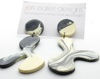 Contemporary handmade black and white lambda earrings