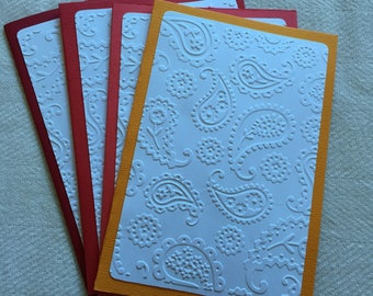 Hand made Embossed note / greetings cards. White Paisley pattern on shades of red & orange. (4 cards). CP06
