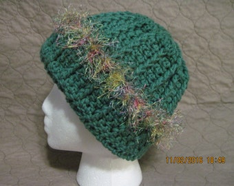 dark sage winter hat with multi-colored rainbow fringe would be a fun gift for St Patrick's Day or a birthday or Christmas present