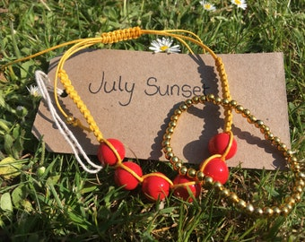 JULY SUNSET - Set of TWO handmade bracelets, one macrame yellow bracelet featuring red beads, one elasticated bracelet with golden pearls