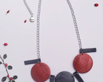 Handmade polymer clay necklace with three discs in dark green and reddish-bronze