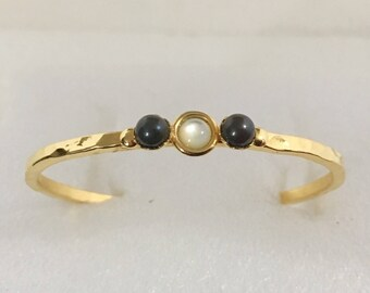 Gold plated brass cuff bracelet with mother of pearl and black onyx stones