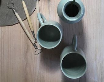 2 white enamel water green stoneware Mugs