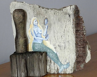 A driftwood sculpture featuring a painted mermaid looking in a mirror.