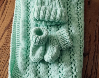 New Born This is a hand knitted baby blanket in a minty green.   It is approximatly 25 in. by 25 in. Perfect size for a stroller.