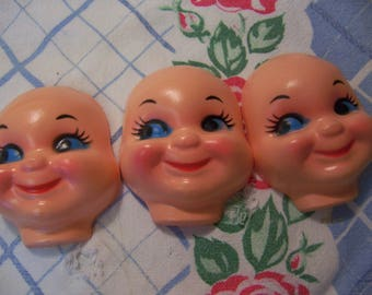 three thin plastic doll faces