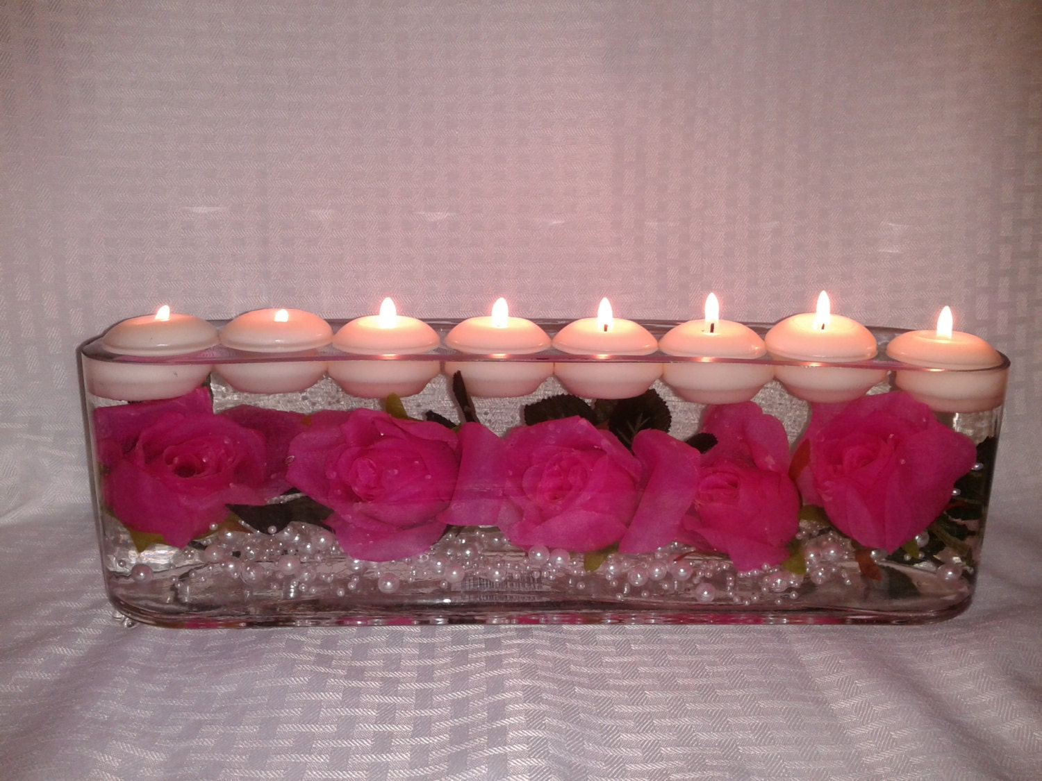 Roses and pearls floating in a long vase with candles
