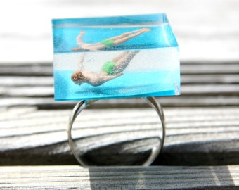 Large square ring adjustable plunge of a male figure resin in a turquoise background