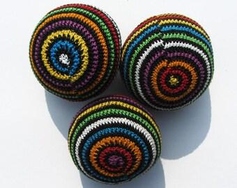 Three multicolored striped juggling balls.