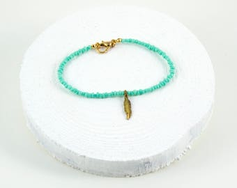 minimalist beaded bracelet with feather accent bead