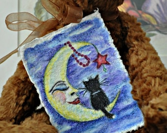 ACEO, Artist Trading Card of a watercolor painting of moon with a black kitty sitting on moon with a red star, red beads hanging from moon