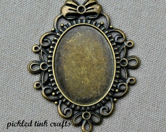 Brass Oval Bezel/Pendant with Floral & Ribbon Border with Bow