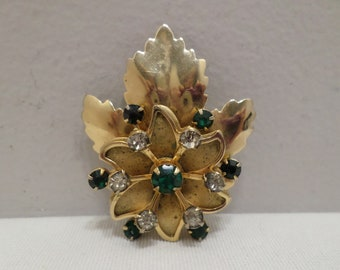 Vintage gold tone metal brooch with green clear and black rhinestones costume jewelry