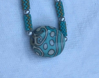 Glass artisan focal bead on chain of beaded cylinder beads
