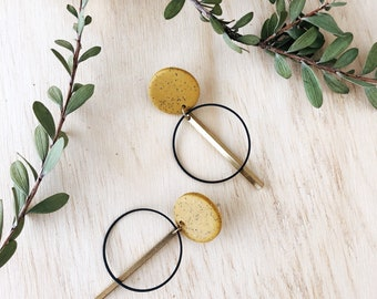 Clay and brass earrings with a large yellow ochre stud.