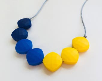 Teething necklace in navy, ultramarine and yellow; made from BPA free chewable silicone quadrate beads by Little Gnashers