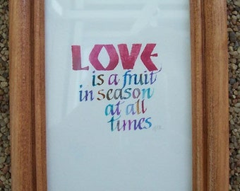 Love is a fruit in season at all times quote in a oak frame