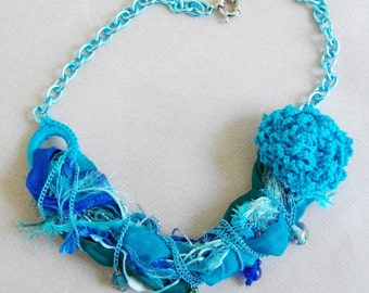 Colorful mixed materials statement necklace in shades of turquoise aqua and emerald green
