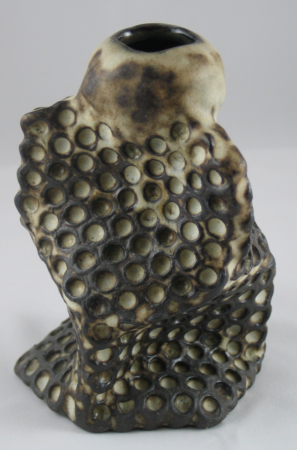 Honeycomb vase mad with a dark clay body and cream colored glaze