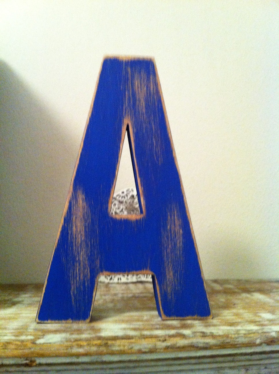 Letter A in Ariel font, painted in Union Jack blue, with heavy distressing