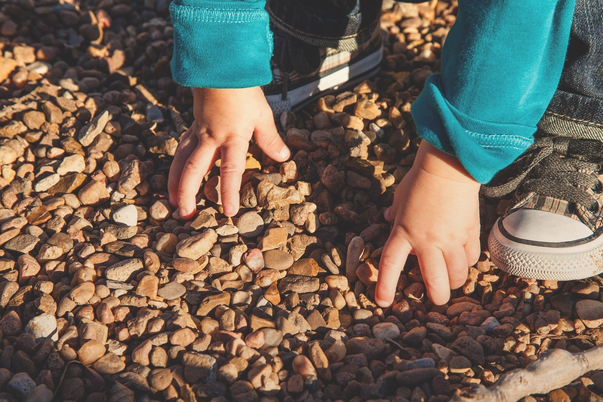 Outdoor play, pebbles, child, explore, sensory