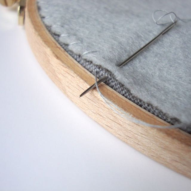Back your embroidery hoop: whipstitch backing felt in place.