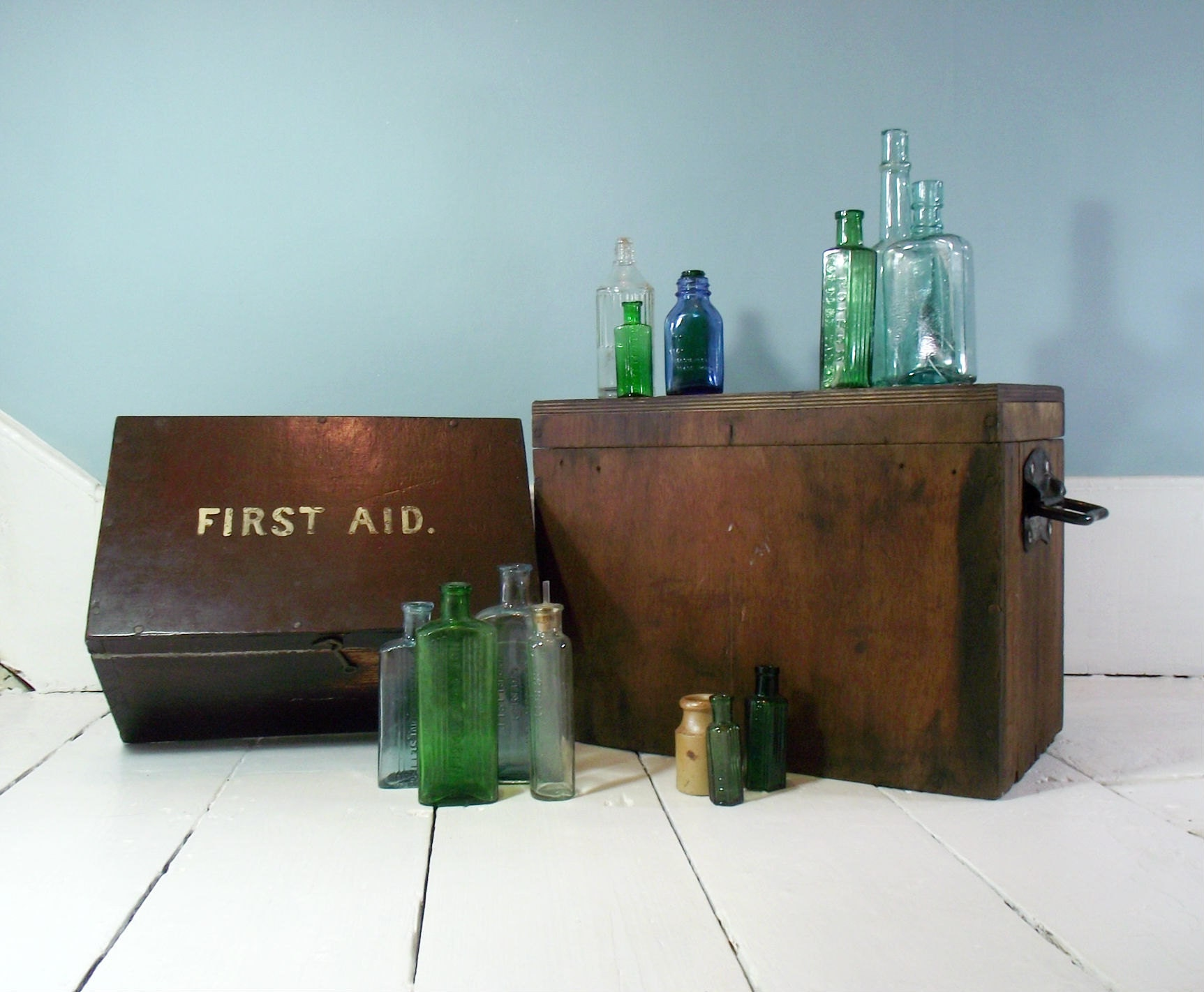 A collection of antique poison bottles and apothecary bottles with a vintage first aid box from the 1920s.